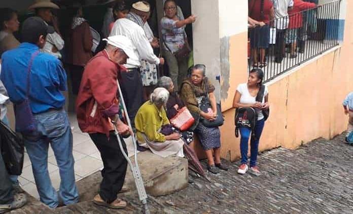Esperan bajo la lluvia la entrega de sus apoyos