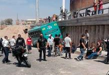Chofer de camión urbano derriba el barandal de una casa y choca contra contención del puente Pemex